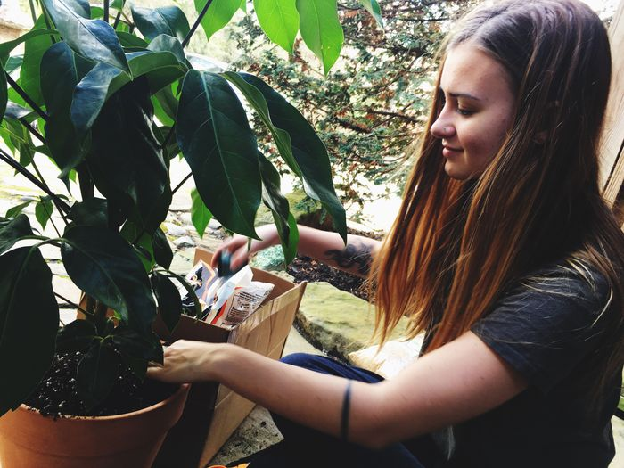 Young woman with hands on tree