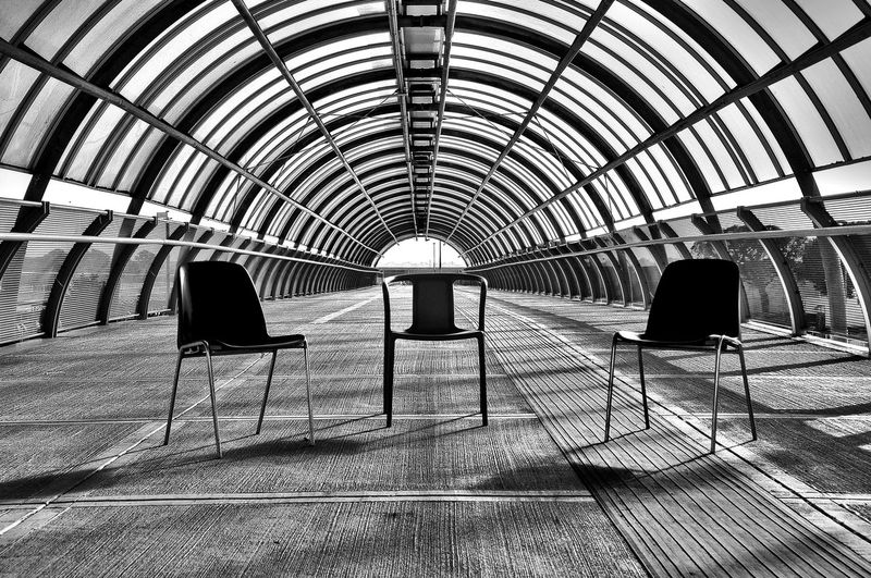 Empty Chairs On Covered Footbridge