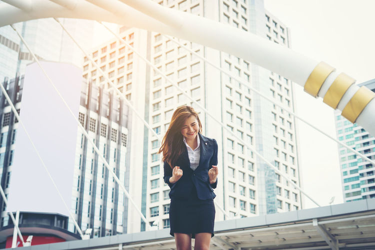 Happy young businesswoman clenching fists against buildings in city
