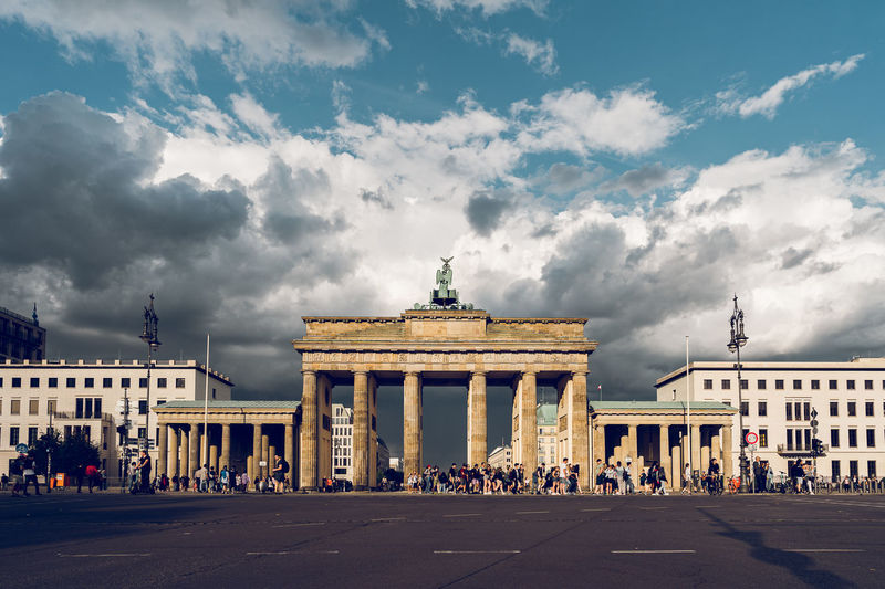 Group of people in front of brandenburg gate and buildings against cloudy sky