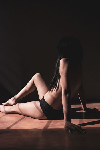 Young woman sitting on floor against black background