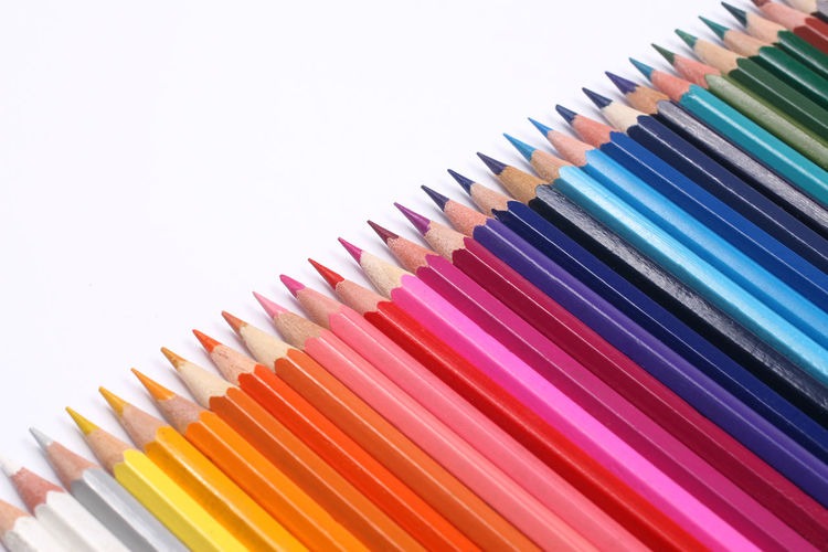 Close-Up Of Colored Pencil Arranged In A Row Against White Background