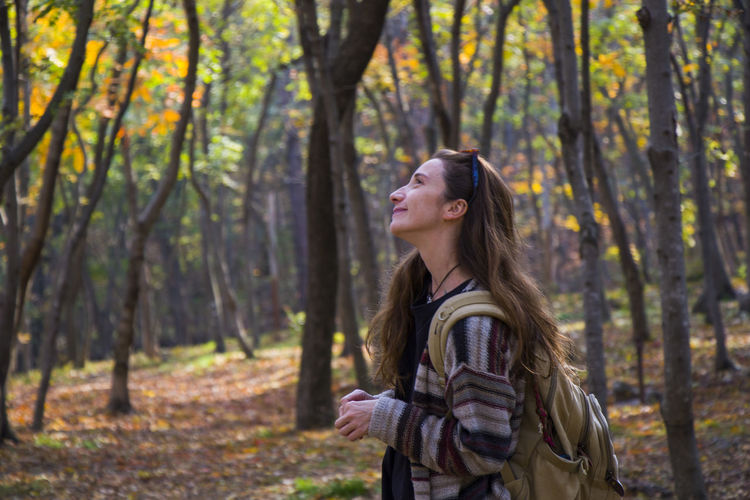 Beautiful woman in autumn and fall forest and wild, autumn tree with yellow and red leaves
