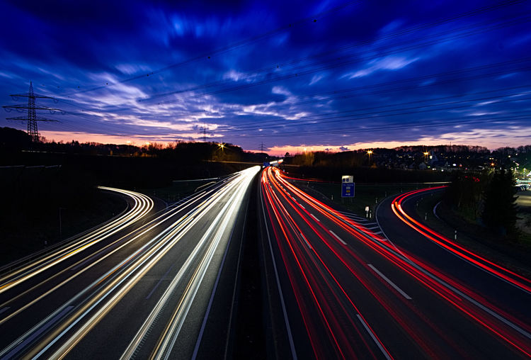 Light Trails On Road Against Dramatic Sky At Night