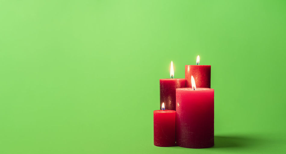 Close-up of burning candle against green background