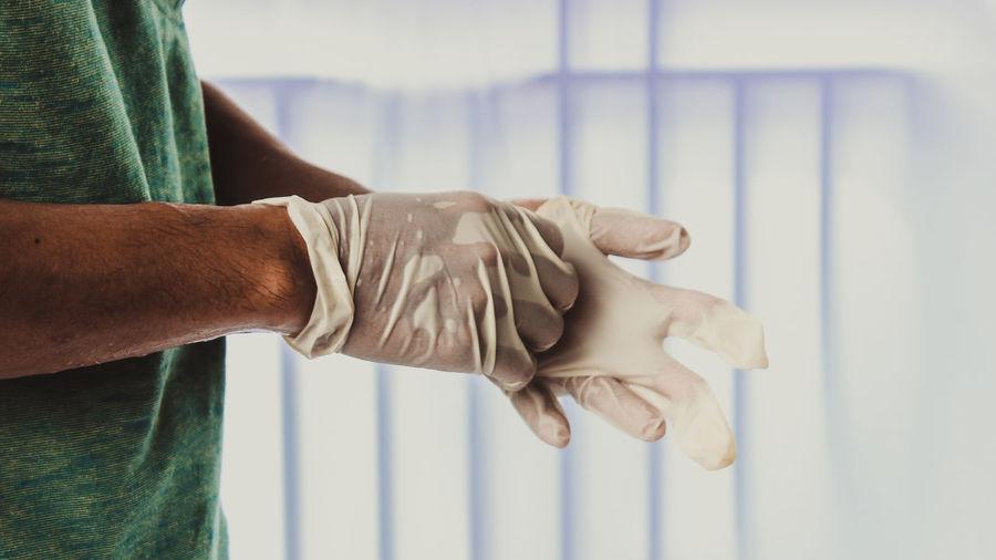 Close-up of man working against white wall