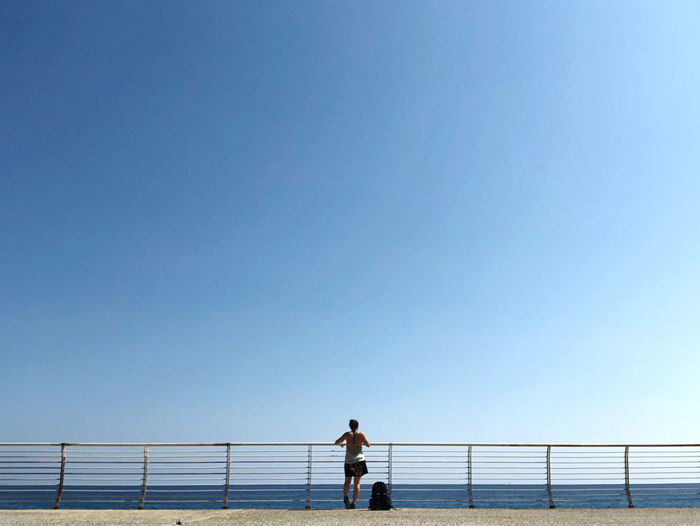 Man standing on railing against clear blue sky