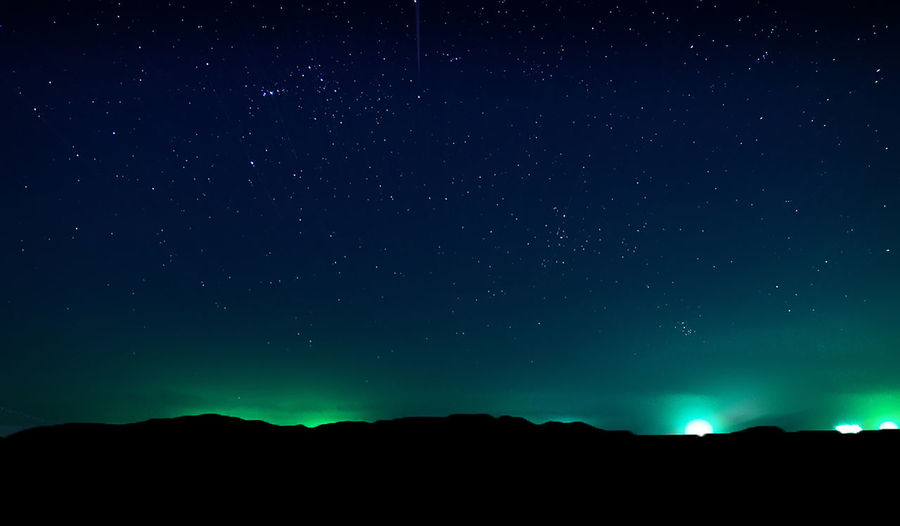 Low angle view of silhouette landscape against star field at night