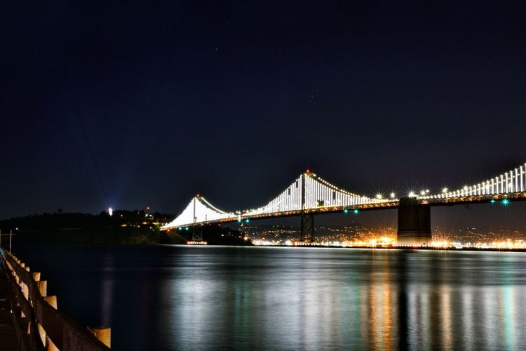 Illuminated bridge over calm river at night