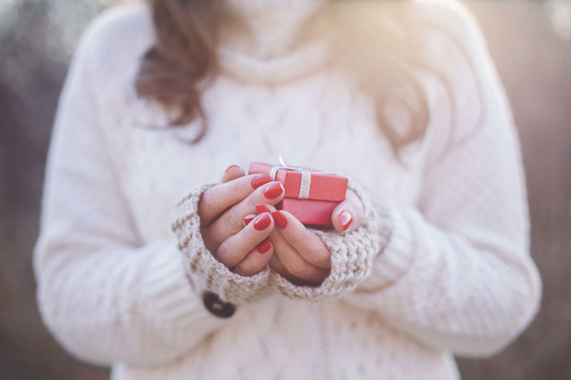Midsection of woman holding gift while wearing sweater