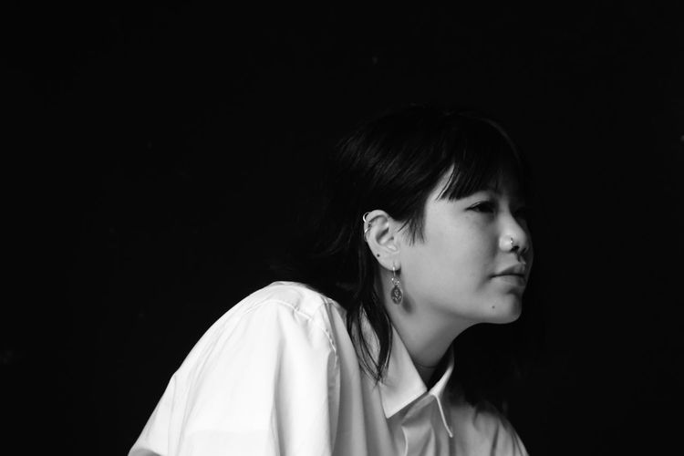 Close-up of thoughtful young woman against black background