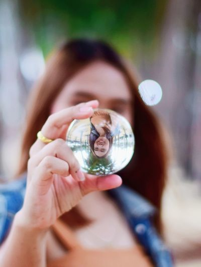 Close-up of woman holding crystal ball against face