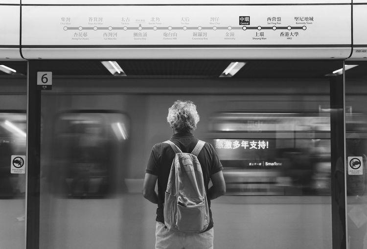 Rear view of man waiting against speeding train