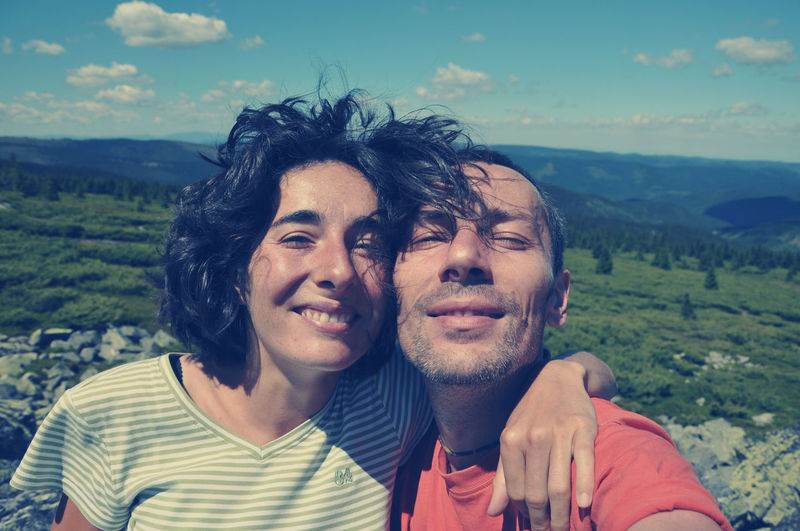 Portrait Of Loving Couple Standing On Mountain Against Sky