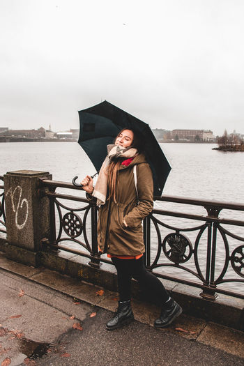 Woman with umbrella standing by railing against river