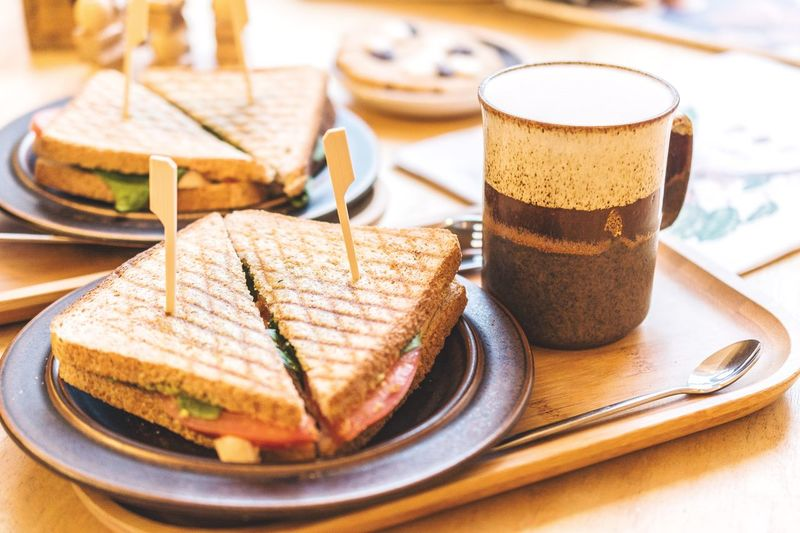 Close-Up Of Toasted Sandwiches With Coffee On Tray At Table