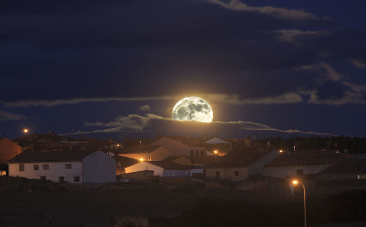 Illuminated houses against sky at night