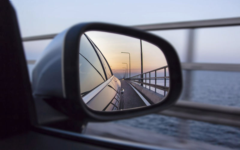 Close-Up Of Car On Bridge Reflecting On Rear-View Mirror