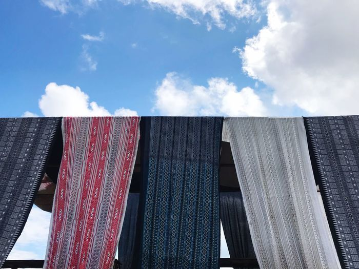 Low angle view of textile hanging against sky