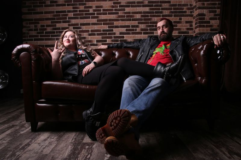 Full Length Of Couple Resting On Sofa Against Brick Wall