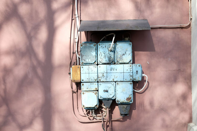 Vintage electricity circuit box, blue on a pink wall, old engineering technology. high voltage