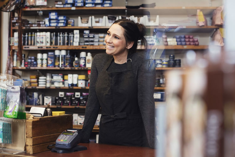 Smiling young woman standing in store