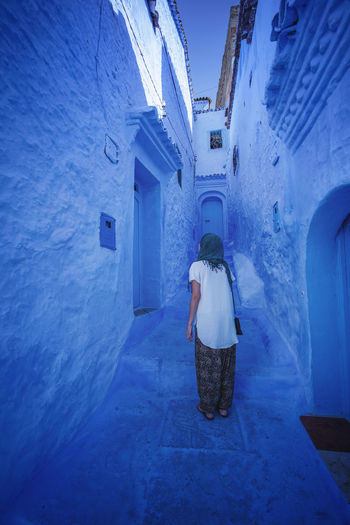 """""""The Blue City"""" We travelled from Sevilla to Tarifa, then took a ferry to Tangier, then a taxi to Chefchaouen, Morocco. EyeEmNewHere a new beginning Chefchaouen Morocco Beauty Blue City Blue Medina Architecture Built Structure One Person Building Lifestyles Women Adult Walking The Way Forward Direction Digital Nomad Building Exterior Leisure Activity Day Standing Men Clothing Outdoors Real People Rear View Full Length Alley Warm Clothing"""