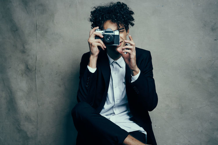 Young man photographing while sitting on wall