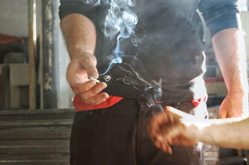 Cropped image of people holding burning cigarette