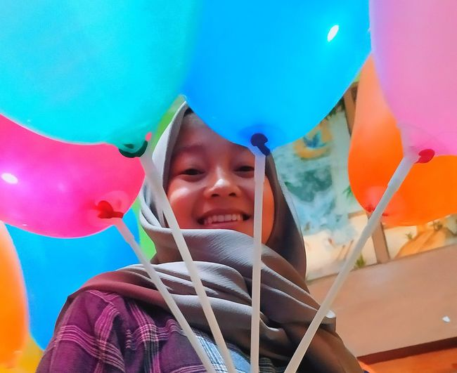 Portrait of smiling girl with multi colored balloons
