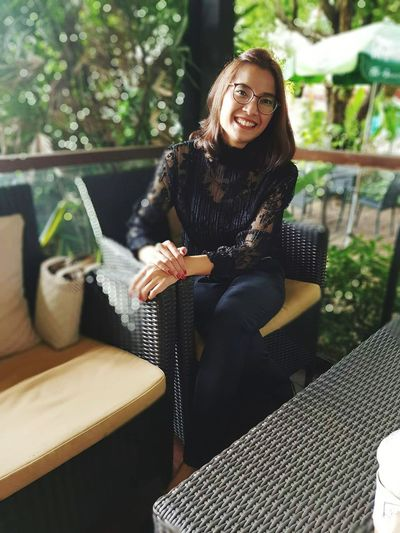 Portrait of smiling woman sitting on chair at cafe