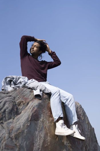 Low angle view of woman sitting on rock against clear sky