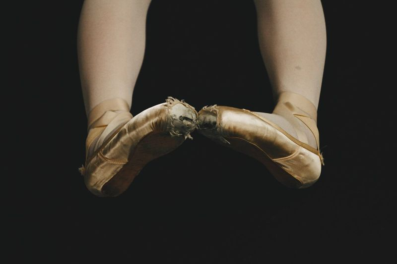 Low section of female ballet dancer with torn shoes against back background