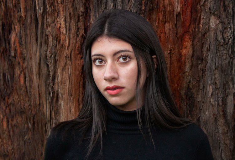 Portrait of a beautiful young woman with tree trunk