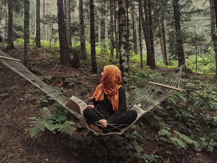 Full length of woman sitting on hammock in forest