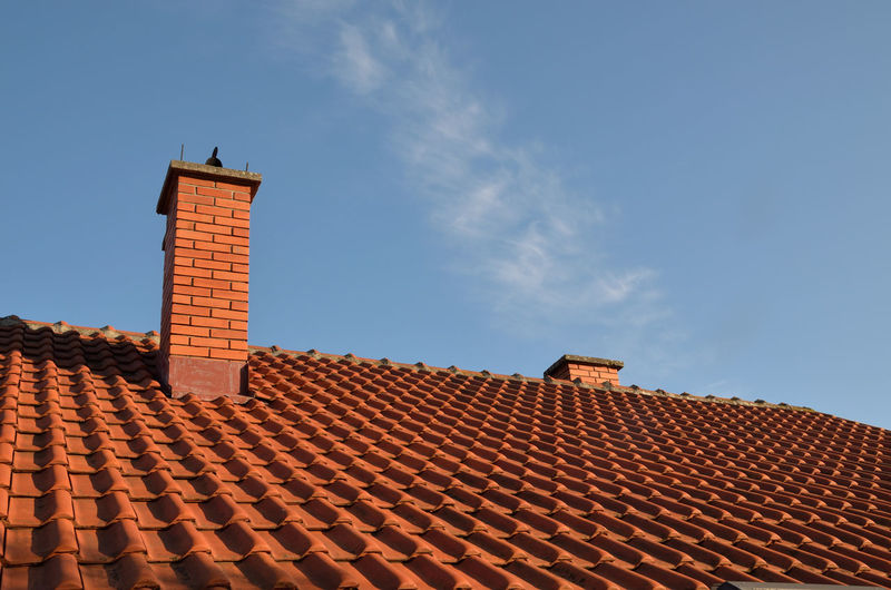 Tiles and chimney on the roof, on a sunny day .