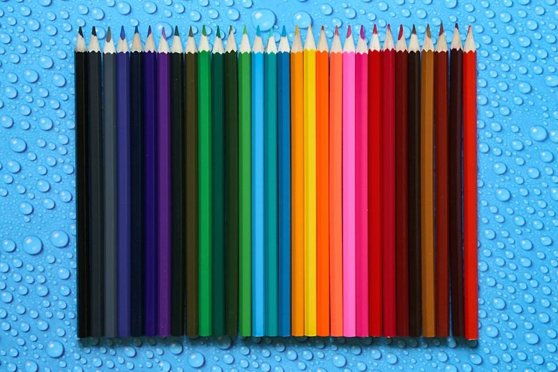 Close-Up Of Colored Pencils On Wet Table