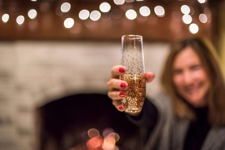 Smiling Mature Woman Holding Champagne Flute Against Defocused Lights
