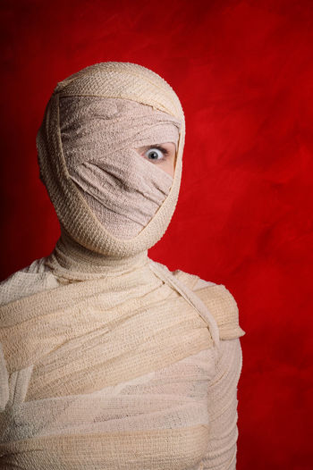 Portrait Of Woman Wrapped With Bandages Against Red Background