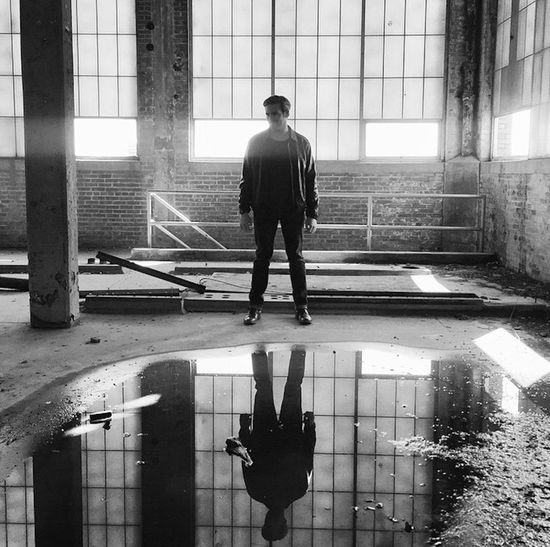 Young man exploring abandoned urban warehouse Architecture Reflection Men Window Fashion Standing Puddle Industrial Style Warehouse A New Beginning Lifestyles Full Length One Person Built Structure Architectural Column Frest Start Urban Landscape Old Building  Looking Down Silhouette Blackandwhite Urban Caucasian Sunlight The Modern Professional Capture Tomorrow