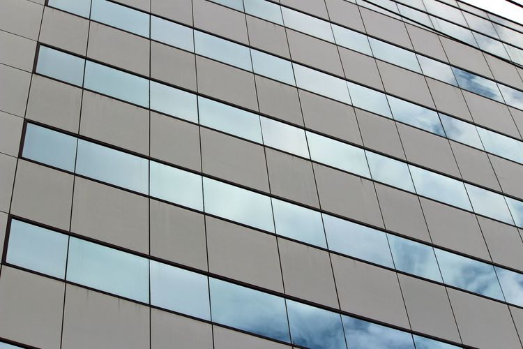 Low angle view of modern building with sky reflecting