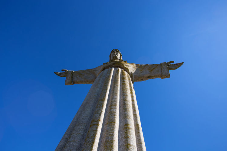 Low angle view of jesus christ statue against clear blue sky