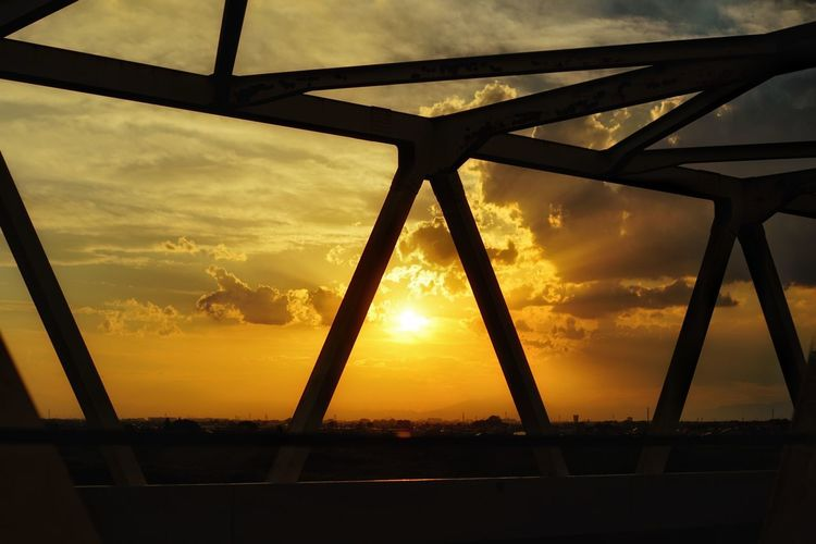 Close-up of silhouette metal against sky during sunset