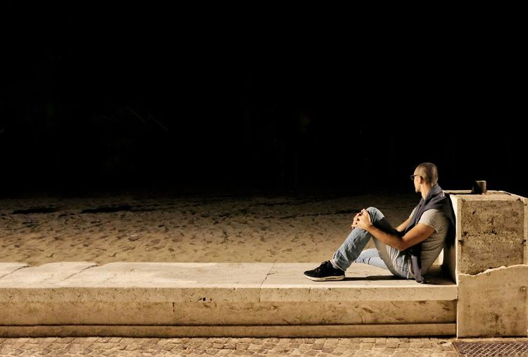 Side view of mid adult man sitting on retaining wall against sky at night
