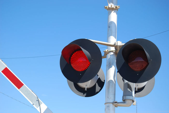 Flashing warning lights at a railroad crossing while the gate is being lowered. Blue Cable Day Electric Light FlashingLights Gates Lighting Equipment Lights Low Angle View No People Outdoors Pole Railroad Red Red Rr RR Crossing Sky Warning