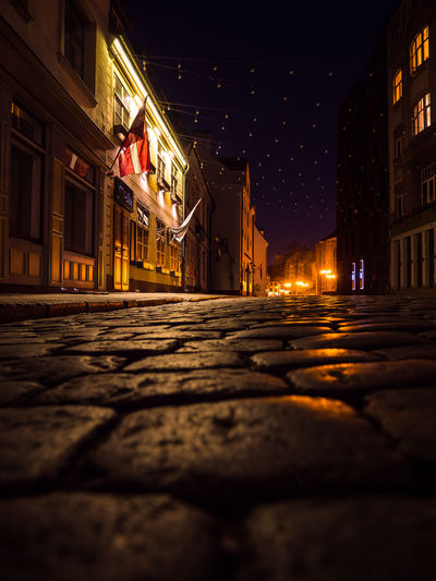 Surface level of illuminated street amidst buildings in city at night