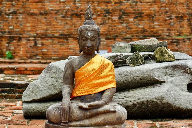 Buddha statue against brick wall