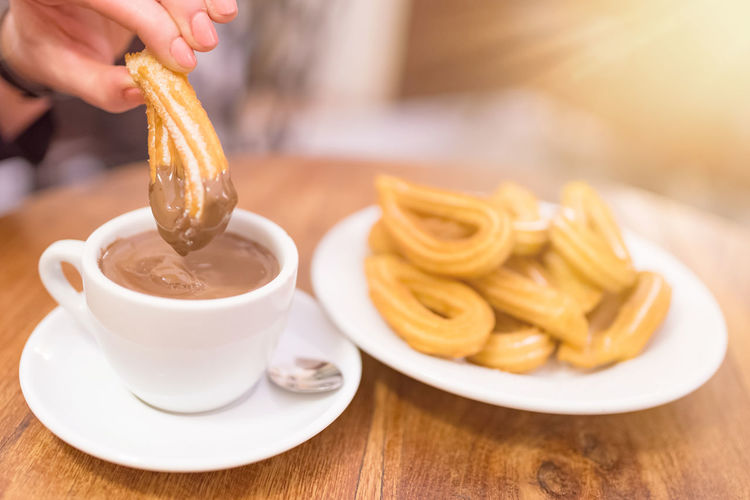 Cropped image of hand dipping food in hot chocolate