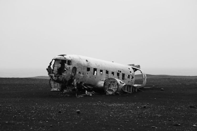 Damaged airplane on field against sky