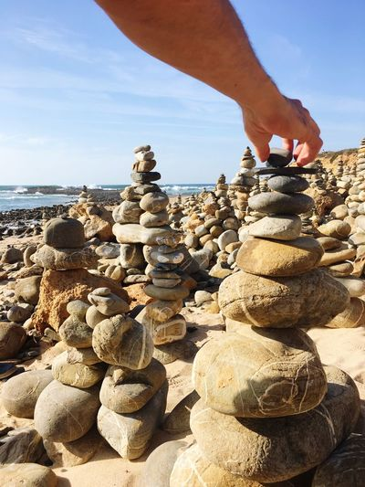 Cropped Hand Of Man Stacking Pebble At Beach Against Sky